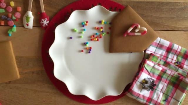 lebkuchen-haus-herstellung-die vergießung kleiner bonbons in schuss - lebkuchenhaus stock-videos und b-roll-filmmaterial