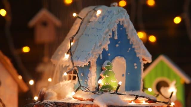 lebkuchen-haus auf dem hintergrund von einer girlande und hölzerne häuser. mit puderzucker bestreuen - lebkuchenhaus stock-videos und b-roll-filmmaterial