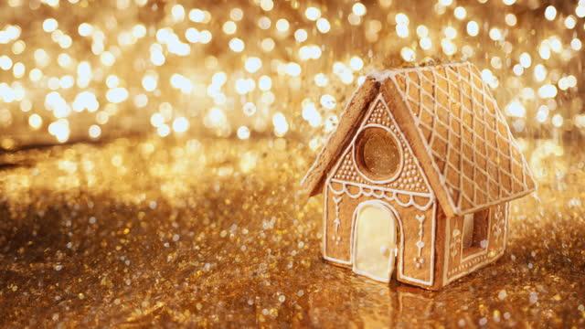 ein lebkuchenhaus mit goldspangles, die oben austreten - lebkuchenhaus stock-videos und b-roll-filmmaterial