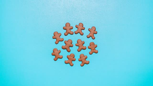 Gingerbread man cookies making of. Cutting and baking cookies. Stop motion with the making of gingerbread man cookies on a blue table. Above view with the gingerbread dough cutting with cookie cutters. gingerbread man stock videos & royalty-free footage