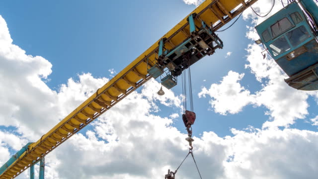 Girder gantry crane moves at construction site. Moving clouds video