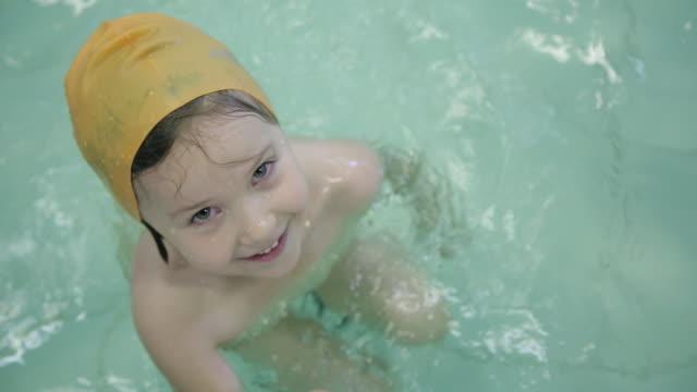 vídeos de stock, filmes e b-roll de menina de 6 anos na piscina. uma menina nada na associação com aletas. - boia salva vidas