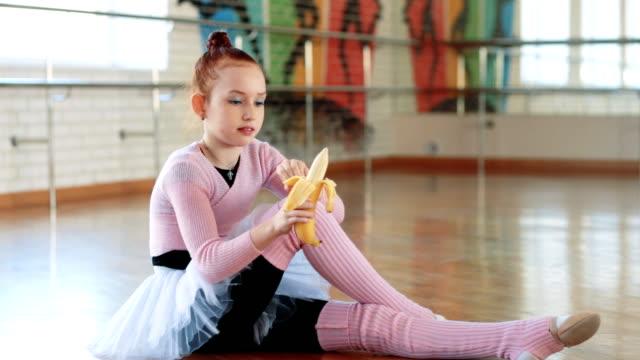 バレエ ホールで運動後の少女は、バナナを食べる。窓際少女。体操。スポーツ。 - 女性選手点の映像素材/bロール