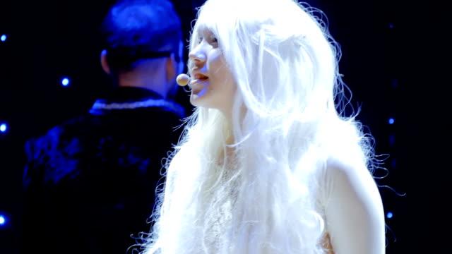 stockvideo's en b-roll-footage met meisje albino en meisje met baard zingen lied op het podium in theater - vetschmink