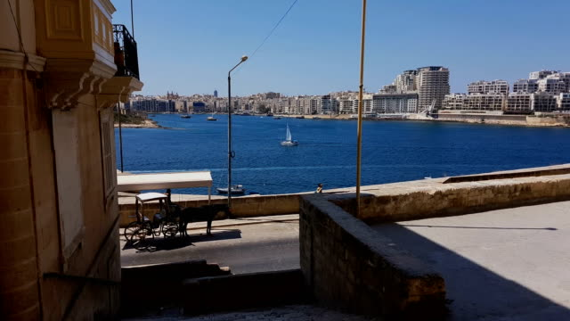 A girl and a boy at Valletta street with a view on Gzira town at Grand Harbor, Malta video