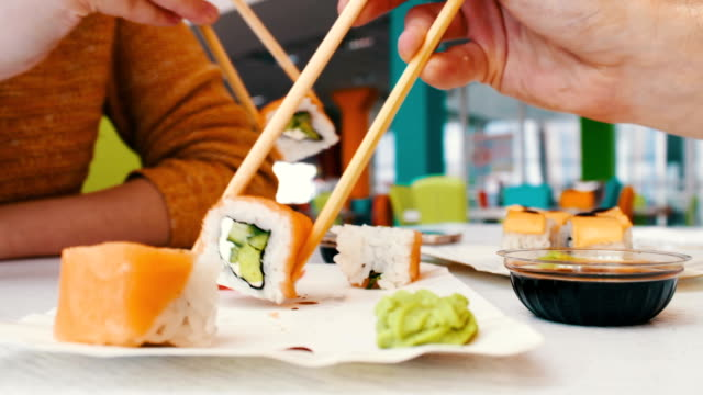 Girl and a guy are sitting in a sushi bar and take with wooden sushi sticks video