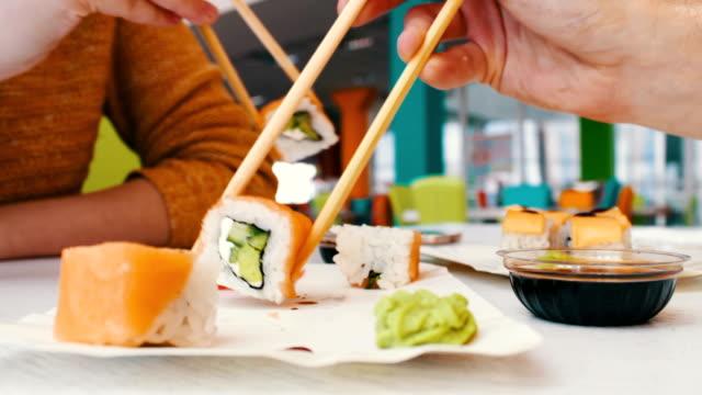 mädchen und ein mann sitzt in einer sushibar und nehmen sie mit hölzernen sushi-sticks - sushi stock-videos und b-roll-filmmaterial