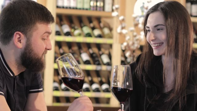a girl and a guy in a restaurant communicate and drink red wine, a young couple drinks red wine at a table in a restaurant or cafe - data scritta video stock e b–roll