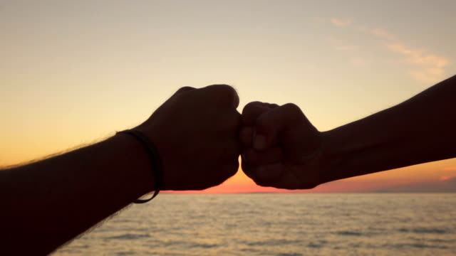 SLOW MOTION, CLOSE UP: Girl and boy bumping fists together as a sign of success video