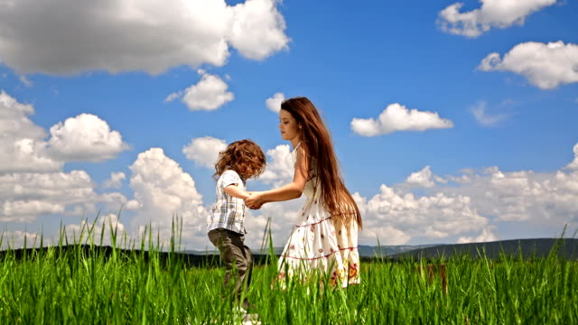 Girl And Boy Jumping In Green Field video