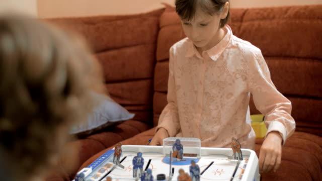vídeos y material grabado en eventos de stock de los niños y niñas jugando al hockey de mesa en casa - tablón