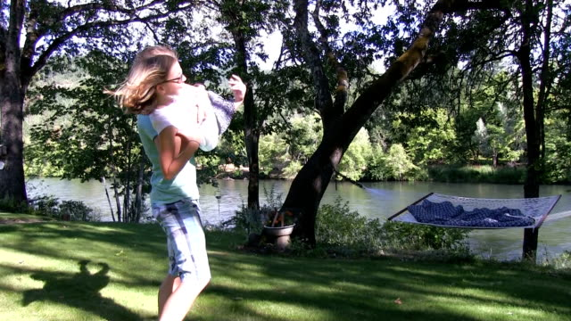 Girl and boy spin on grass slow motion 75% video