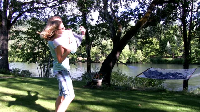 Girl and boy spin on grass v2 slow motion 50% video