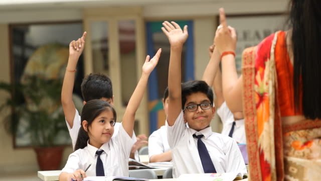 Girl and boys raising hand in classroom Smiling girl and boys raising her hand to answer a question in classroom indian culture stock videos & royalty-free footage