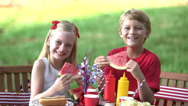 Girl and brother at fourth of July picnic An 8 year old girl and her 9 year old brother sitting together at a picnic table eating watermelon and hot dogs. The decorations are red, white and blue to celebrate July 4th or memorial day. family 4th of july stock videos & royalty-free footage