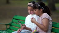 istock Girl and friends using smart phone and sitting on chair in the park 1211412555