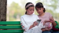 istock Girl and friends using smart phone and sitting on chair in the park 1211418922
