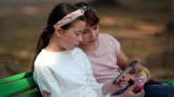 istock Girl and friends using smart phone and sitting on chair in the park 1211428535