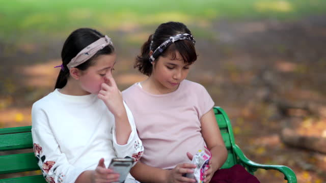 Girl and friends using smart phone and sitting on chair in the park