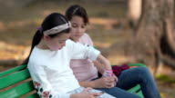 istock Girl and friends using smart phone and sitting on chair in the park 1211445550