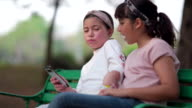 istock Girl and friends using smart phone and sitting on chair in the park 1211449353