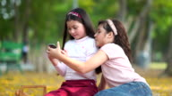 istock Girl and friends using smart phone and sitting on ground in the park 1211491089
