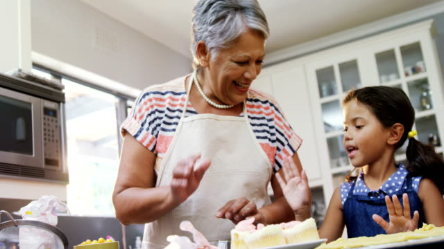 Girl and grandmother giving a high-five while preparing cookies 4K 4k video