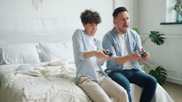 vídeos de stock e filmes b-roll de girl and guy couple enjoying video game sitting in bed in apartment having fun - man joystick