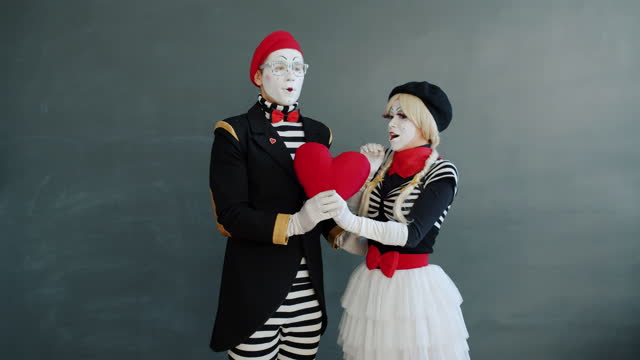 Girl and guy mimes showing heart gestures then kissing on grey background