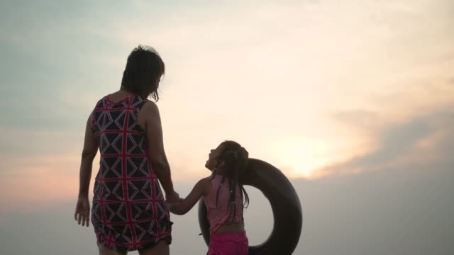 A girl and her grandmother standing at beach