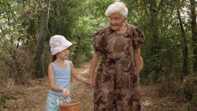 A Girl And Her Grandmother Walk The Dusty Country Road. Real People, Rural Scene, Unusual Angle. video