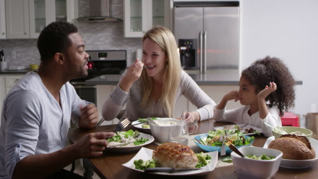 girl and her mixed race parents dining in their kitchen, shot on r3d - kitchen room video stock e b–roll