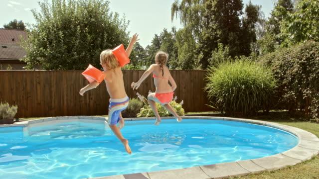 vídeos y material grabado en eventos de stock de cámara lenta cs joven hermano y hermana salto en piscina - backyard pool