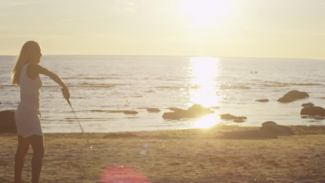 Girl and Man are Playing in Badminton on the Beach at Sunset Time video