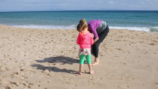 vidéos et rushes de fille et mère collecte de conches sur la plage - coquille et coquillage