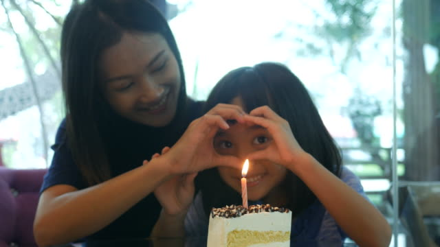 girl and mother enjoy with birthday's cake , hand play heart sign video