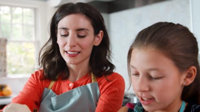 vídeos de stock e filmes b-roll de girl and mother preparing dough for challah bread, close up - baking bread at home