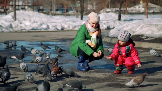 Girl and Woman Feeding Pigeons with Bread Crumbs