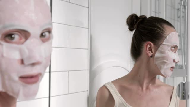 flicka som tillämpar mask på hennes ansikte som tittar i spegeln - japanese bath woman bildbanksvideor och videomaterial från bakom kulisserna