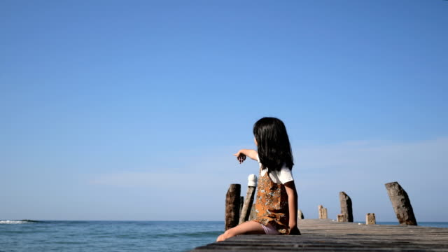 Girl Asian on wooden bridge on seaside