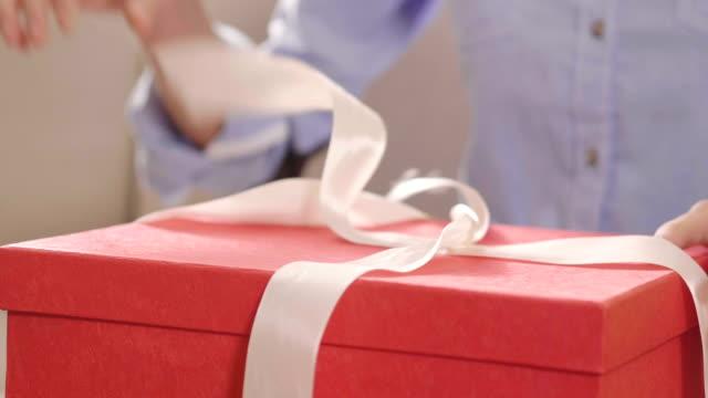 家にいる女の子が到着したギフトバッグを開きます。 - プレゼント点の映像素材/bロール