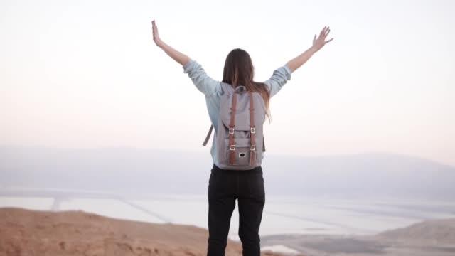 vídeos y material grabado en eventos de stock de chica en la cima de la montaña, amplia los brazos abiertos. cámara lenta. viajero mujer europea bastante emocionado. felicidad. desierto de israel - recuerdos