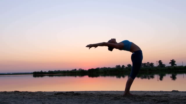 Girl at sunset showing gymnastic exercises video
