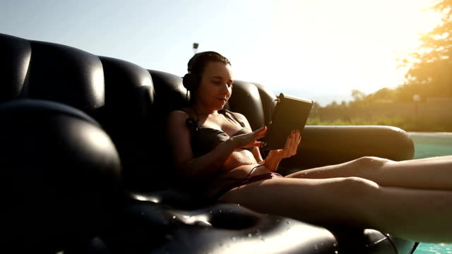 Girl at the swimming pool with digital tablet video