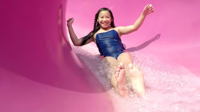flicka på water park glida ner vattenrutschkana - fritidsanläggning bildbanksvideor och videomaterial från bakom kulisserna