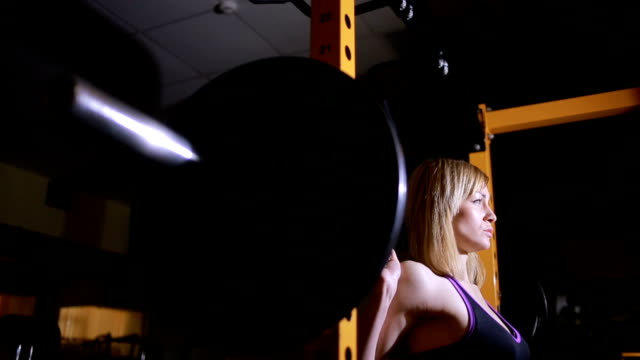 girl athlete doing exercises with barbell in gym video