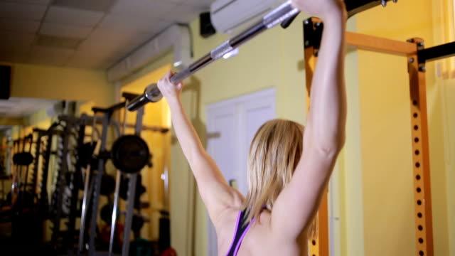 girl athlete doing exercises with barbell in gym - giuntura umana video stock e b–roll