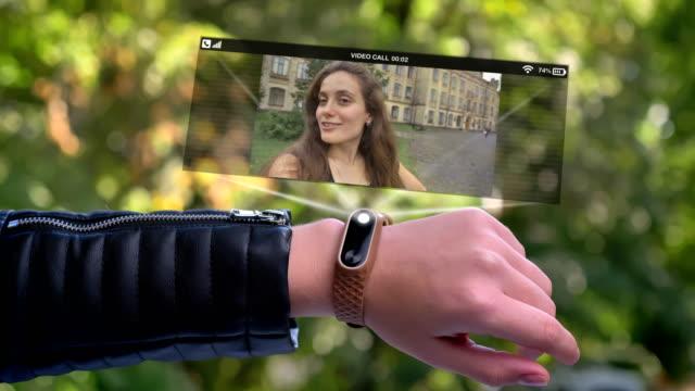 vídeos de stock, filmes e b-roll de amigo da chamada da mão do atleta da menina que aparece no holograma. relógio futurista e tecnológico. parque no fundo. - holograma