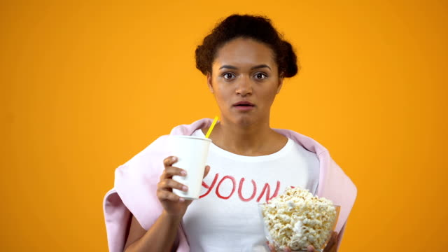 vídeos de stock, filmes e b-roll de menina atentamente assistindo filme e beber refrigerantes, influência da televisão - balde pipoca