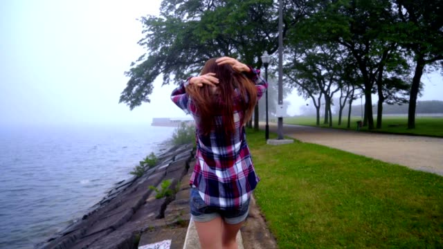 Girl back view. Walking woman near sea in the park. Style woman going back view video